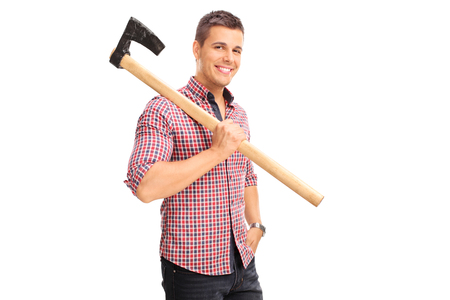 shoulder carrying: Young guy in a checkered shirt carrying an axe over his shoulder and looking at the camera isolated on white background