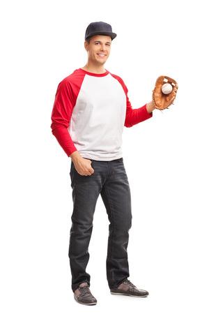 hombre con sombrero: Retrato de cuerpo entero de un hombre joven sosteniendo una pelota de béisbol y mirando a la cámara aislada en el fondo blanco