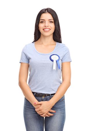 mujer sola: Tiro vertical de una joven alegre, con una insignia azul premio en su camisa aislada en el fondo blanco