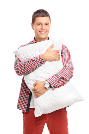 look pleased: Vertical shot of a content young man hugging a white pillow and looking at the camera isolated on white background