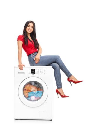 Full length Portret van een mooie jonge vrouw, zittend op een wasmachine en op zoek naar de camera op een witte achtergrond