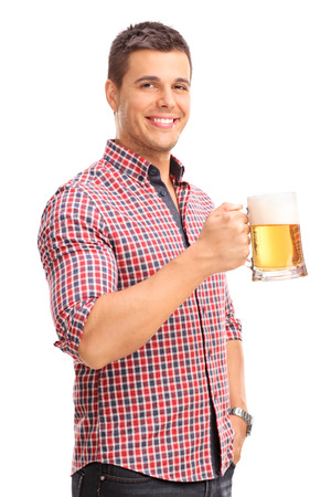 hombre tomando cerveza: Tiro vertical de un joven alegre que sostiene una taza de cerveza llena de cerveza y sonriente aislados sobre fondo blanco Foto de archivo