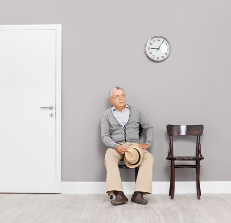 office wall: Bored senior gentleman sitting in an office lobby on wooden chairs with a clock on the wall behind him