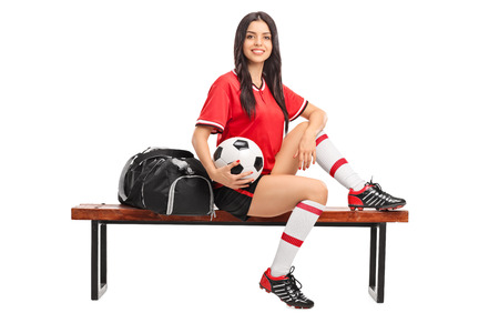player bench: Studio shot of a female football player in a red jersey sitting on a bench with a black sports bag beside her isolated on white background