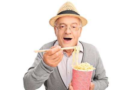 chinesisch essen: Älterer Herr Essen chinesisches Essen mit Stöcken und schaut in die Kamera isoliert auf weißem Hintergrund