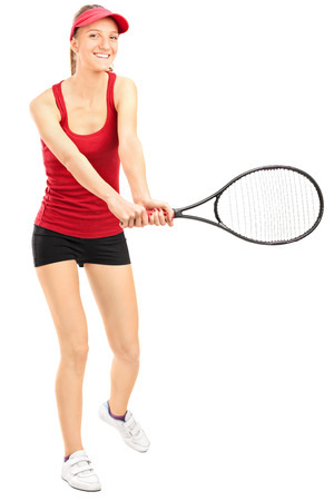 Full length portrait of a female tennis player swinging a racquet and looking at the camera isolated on white background photo