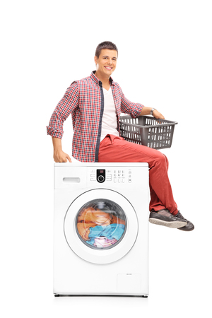 clothes: Young man waiting for the washing machine to finish seated on top of it and holding an empty plastic basket isolated on white background