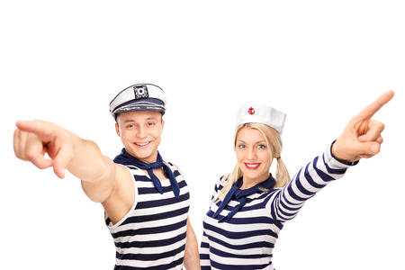 sailor hat: Male and female sailor pointing up with their fingers and looking at the camera isolated on white background