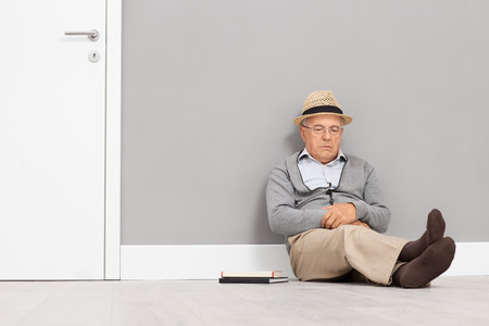 old man sitting: Senior gentleman sleeping seated on the floor and leaning against a wall next to a white door with a couple of books next to him
