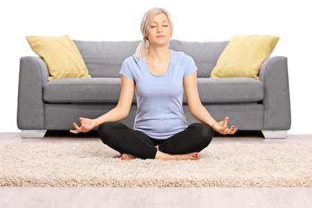 single: Peaceful blond woman meditating seated on the floor in front of a gray sofa isolated on white background Stock Photo