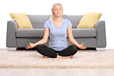 personen: Vreedzame blonde vrouw mediteren op de grond zitten in de voorkant van een grijze bank die op een witte achtergrond