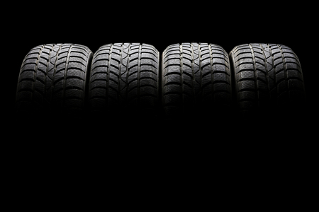 Studio shot of a set of four black car tires lined up horizontally in a dark ambient on black background Foto de archivo
