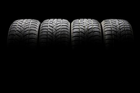 llantas: Tiro del estudio de un conjunto de cuatro neumáticos del coche negro alineados horizontalmente en un ambiente oscuro sobre fondo negro