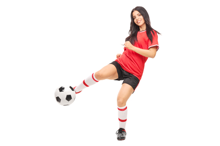 female soccer: Cheerful female soccer player shooting a ball and looking at the camera isolated on white background