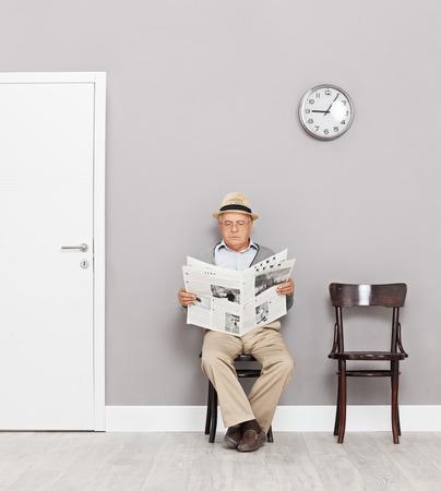persona leyendo: Señor mayor que se sienta en sillas de madera en una sala de espera y la lectura de un periódico tiro con inclinación y desplazamiento de la lente