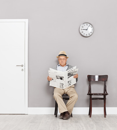 person reading: Senior gentleman sitting on wooden chairs in a waiting room and reading a newspaper shot with tilt and shift lens