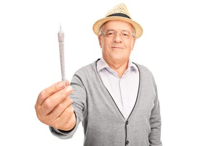 Freundliche fällige Mann, der medizinisches Marihuana in Richtung der Kamera isoliert auf weißem Hintergrund