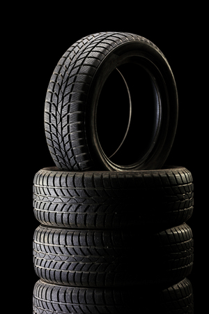 ambient: Vertical shot of a stack of tires in a dark ambient on black background Stock Photo