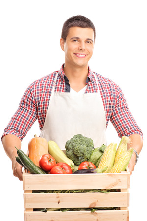 seller: Vertical shot of a young man with a white apron holding a wooden crate full of fresh vegetables and looking at the camera isolated on white background