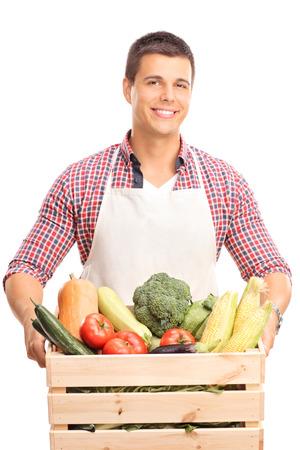 Vertikale Schuss von einem jungen Mann mit einer weißen Schürze, eine Holzkiste voll mit frischem Gemüse und schaut in die Kamera isoliert auf weißem Hintergrund