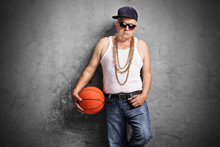 sullen: Sullen senior rapper holding a basketball and leaning against a rusty gray wall Stock Photo