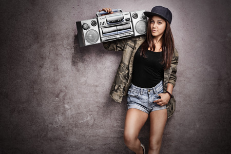 Teenage girl carrying a ghetto blaster over her shoulder and leaning against a rusty gray wall