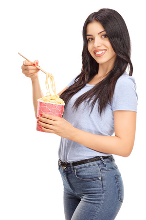 asian adult: Vertical shot of a beautiful woman eating Chinese food with sticks and looking at the camera isolated on white background
