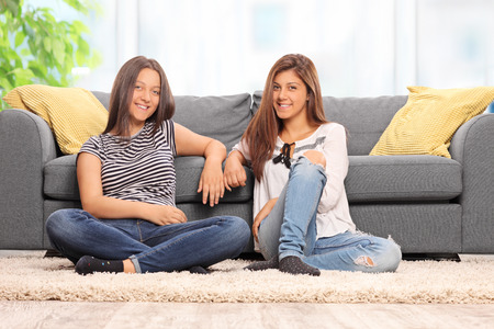 girl home: Two happy teenage girls sitting on the floor in front of a modern gray sofa at home