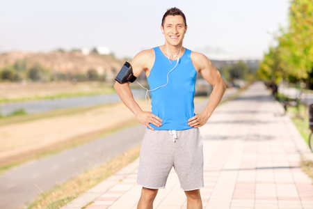 hombre deportista: Male athlete listening to music on his cell phone and standing on a sidewalk