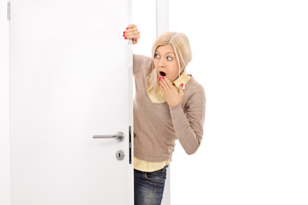 peek: Blond woman peeking from behind a door and making shocked grimace isolated on white background