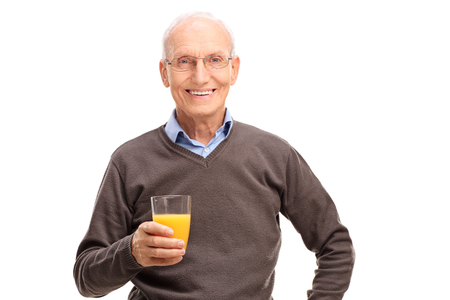 70s adult: Joyful senior holding a fresh orange juice and looking at the camera isolated on white background Stock Photo