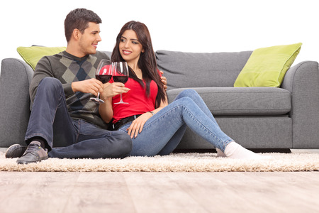 tomando alcohol: Joven pareja beber vino tinto sentado en el suelo delante de un sof� gris aislado en el fondo blanco Foto de archivo