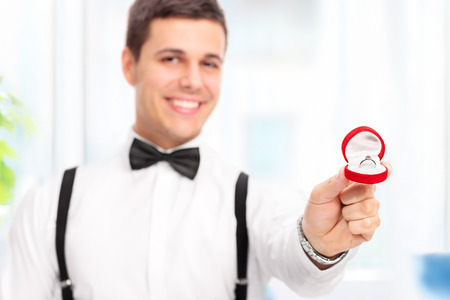 anillo de compromiso: Hombre joven elegante que propone con un anillo de compromiso en su casa con el foco en el anillo