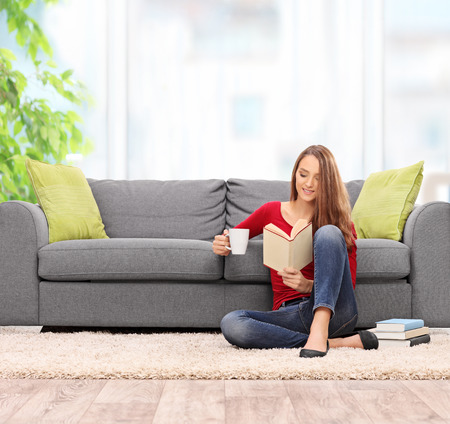 本を読んで、自宅にグレーのソファの前の床の上に座ってコーヒーを飲む若い女性の傾きで撮影し、レンズをシフト 写真素材
