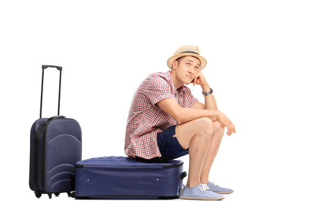 Bored male tourist sitting on his baggage and looking in the distance isolated on white background
