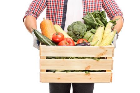 Close-up op een man met een houten kist vol verse groenten op een witte achtergrond Stockfoto