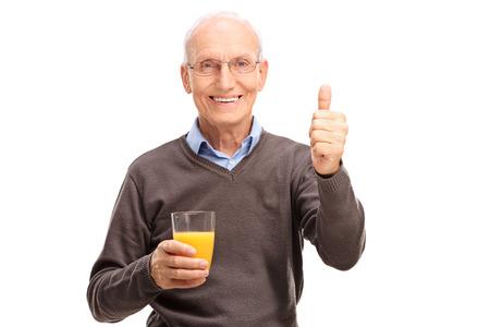 posing  agree: Joyful senior holding an orange juice and giving a thumb up isolated on white background