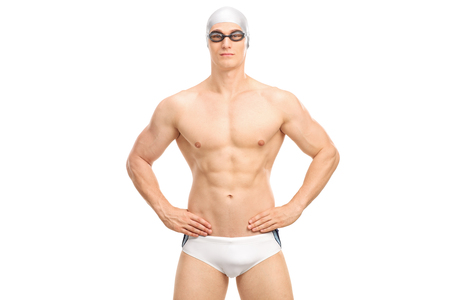 hunk: Handsome young swimmer in white swim trunks and black swimming goggles isolated on white background Stock Photo
