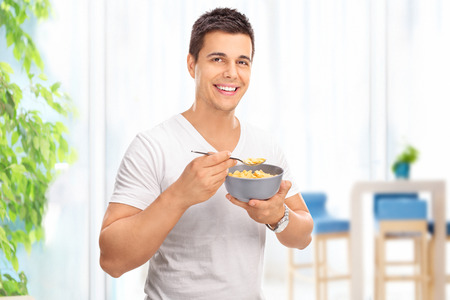 Young cheerful man eating cereal from a bowl and looking at the camera at home