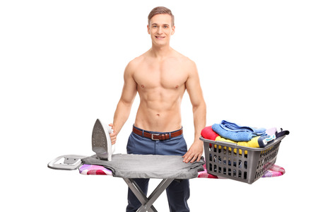 Young shirtless man posing behind an ironing board with a basket full of clothes on it isolated on white background
