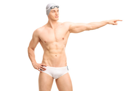 male hand: Young handsome male swimmer in white swim trunks pointing with his hand towards right isolated on white background