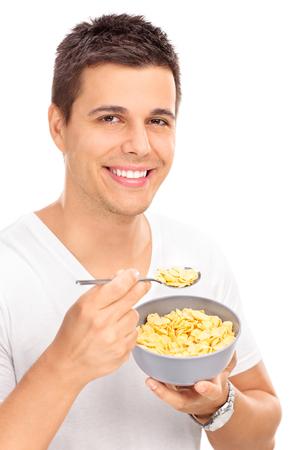 comiendo cereal: Tiro vertical de un joven alegre que come el cereal con una cuchara de un cuenco y mirando a la cámara aislada en el fondo blanco Foto de archivo