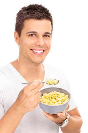 man eating: Vertical shot of a cheerful young man eating cereal with a spoon from a bowl and looking at the camera isolated on white background
