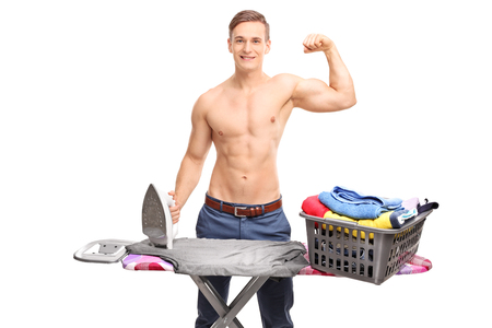goodlooking: Good-looking shirtless guy posing behind an ironing board and showing his bicep isolated on white background