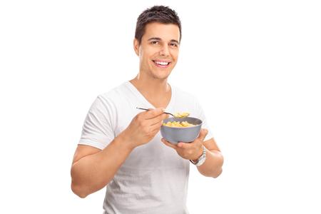 cereal: Hombre joven alegre que come el cereal de un tazón y mirando a la cámara aislada en el fondo blanco