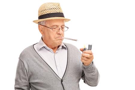 Senior man het aansteken van een joint met een grijze lichter geïsoleerd op een witte achtergrond