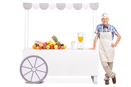 jerk: Senior soda jerk standing next to a stall with a juicer and a bunch of fresh fruits on it isolated on white background