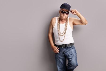hombre con sombrero: Gángster mayor que desgasta la ropa de hip-hop y accesorios y apoyado contra una pared gris