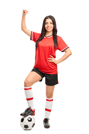 soccer player: Full length portrait of a young female soccer player stepping over a ball and gesturing happiness isolated on white background Stock Photo