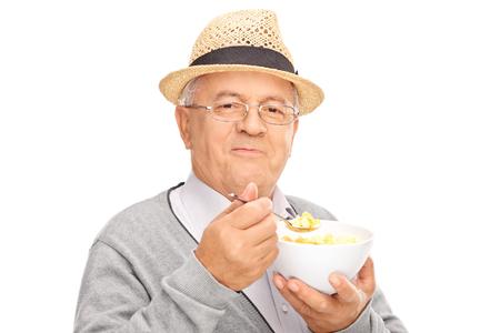 persona mayor: Studio foto de un señor mayor que come el cereal de un tazón y mirando a la cámara aislada en el fondo blanco